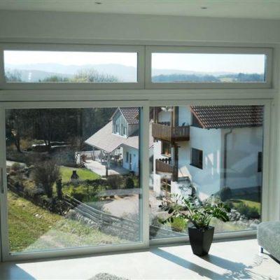 zwei-grosse-weisse-Fensterelemente-mit-Hebe-Schiebe-Tuer-mit-Ausblick-auf-Garten-und-Nachbarhaus