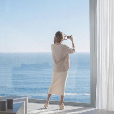 Eine Frau mit dem Blick aufs Meer vor einem Fenster mit einem sehr hohen Glasfaseranteil und dem Faserverbundwerkstoff RAU-FIPRO X