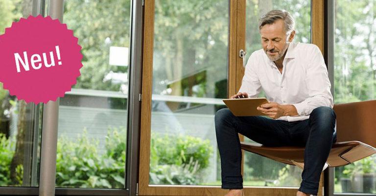 Ein Mann auf einem Holzstuhl vor Fenstern aus Kunststoff in Holzoptik, die Kaleido Woodec