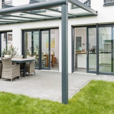 dunkelgraue-hebeschiebetuer-verbindet-Terrasse-und-Wohnbereich-eines-Hauses