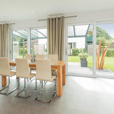 weisse-hebeschiebetuer-trennt-helles-Wohnzimmer-von-Terrasse-und-Garten